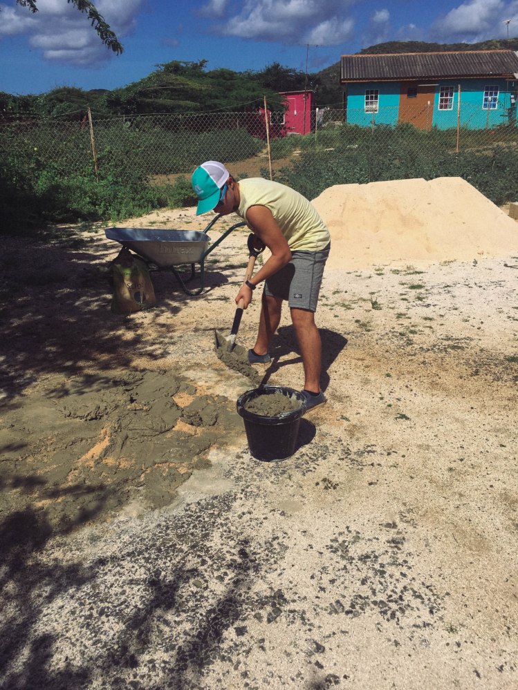 Leo shoveling cement for church walls.
